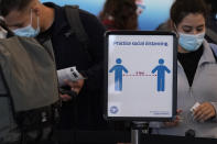 Travelers wait to check-in for their flights as a sign reminding travelers to social distance is displayed in Terminal 3 at O'Hare International Airport in Chicago, Friday, July 2, 2021. (AP Photo/Nam Y. Huh)