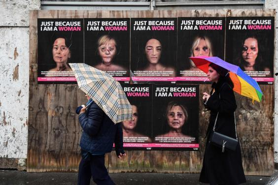 People walk past 'Just because I am a Woman', a new series of works by Italian artist aleXsandro Palombo, depicting women in politics as victims of gender violence (AFP via Getty Images)