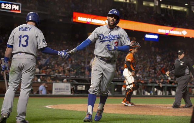 Los Angeles Dodgers' Chris Taylor (3) gets a congratulatory handshake from teammate Max Muncy after hitting a solo home run against the San Francisco Giants during the eighth inning of a baseball game, Friday, June 7, 2019, in San Francisco. The Giants defeated the Dodgers 2-1. (AP Photo/D. Ross Cameron)
