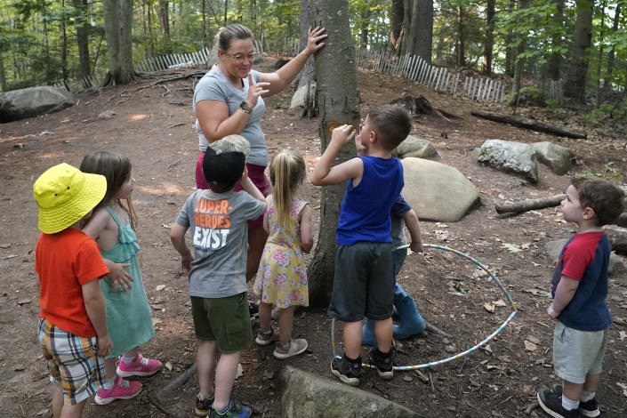 In this July 26, 2021 photo, Jennifer Briggs-Legere teaches a nature lesson to children at her A Place To Grow daycare center in Brentwood, N.H. Families are starting to spend the money from the expanded child tax credit, part of President Joe Biden's $1.9 trillion coronavirus relief package. Many say they are using the money to pay rent, supplement their grocery budgets and for catching up on bills, including cellphone and car payments. Biden increased the amounts going to families and has expanded it to include those whose income is so little they don't owe taxes. (AP Photo/Elise Amendola)