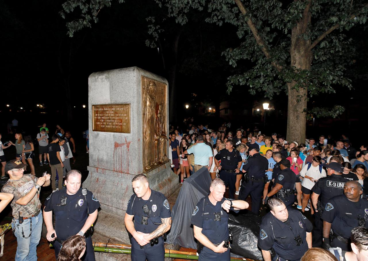 <p>University of North Carolina police stand guard in front of the plinth upon which the toppled statue of a Confederate soldier nicknamed Silent Sam once stood, on the school's campus after a demonstration for its removal in Chapel Hill, N.C., Aug. 20, 2018. (Photo: Jonathan Drake/Reuters) </p>