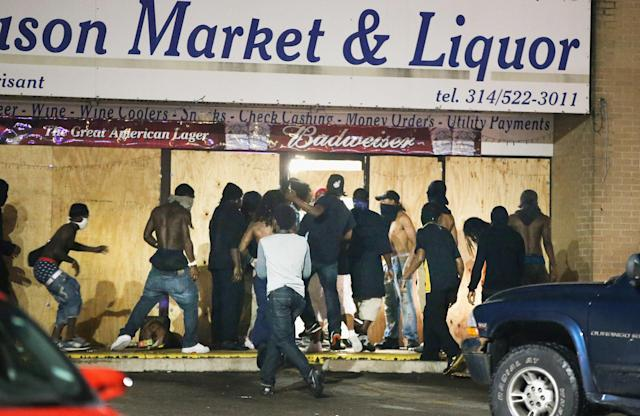 <p>People loot the Ferguson Market and Liquor store on August 16, 2014 in Ferguson, Missouri. Several businesses were looted as police held their position nearby. Violent outbreaks have taken place almost daily in Ferguson since the shooting of Michael Brown by a Ferguson police officer on August 9. (Scott Olson/Getty Images) </p>