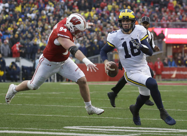 """Michigan's <a class=""""link rapid-noclick-resp"""" href=""""/ncaaf/players/263464/"""" data-ylk=""""slk:Brandon Peters"""">Brandon Peters</a> runs past Wisconsin's Conor Sheehy during an NCAA college football game Saturday, Nov. 18, 2017, in Madison, Wis. (AP Photo/Aaron Gash)"""