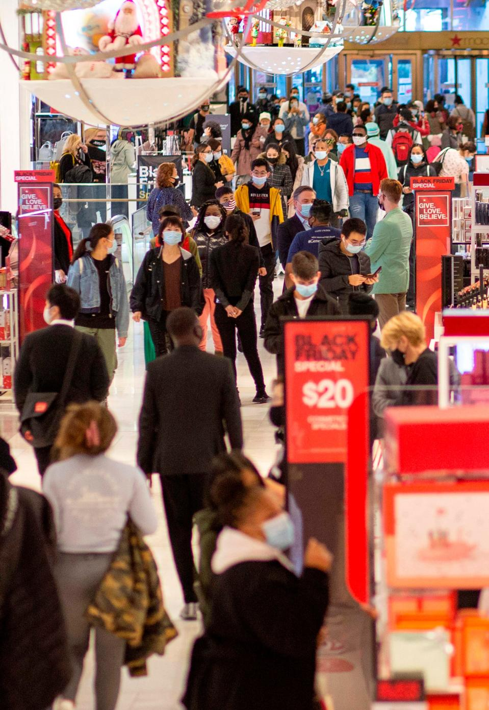 "Customers shop at Macys department store in New York on Black Friday, November 27, 2020. - The coronavirus is clouding ""Black Friday"" much as it has overshadowed 2020 in general, but some leading experts still expect strong overall sales even as shopping patterns are altered."