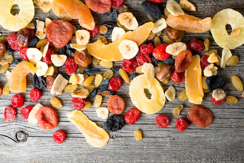 Mix of dried and candied fruit on a wooden background, top view