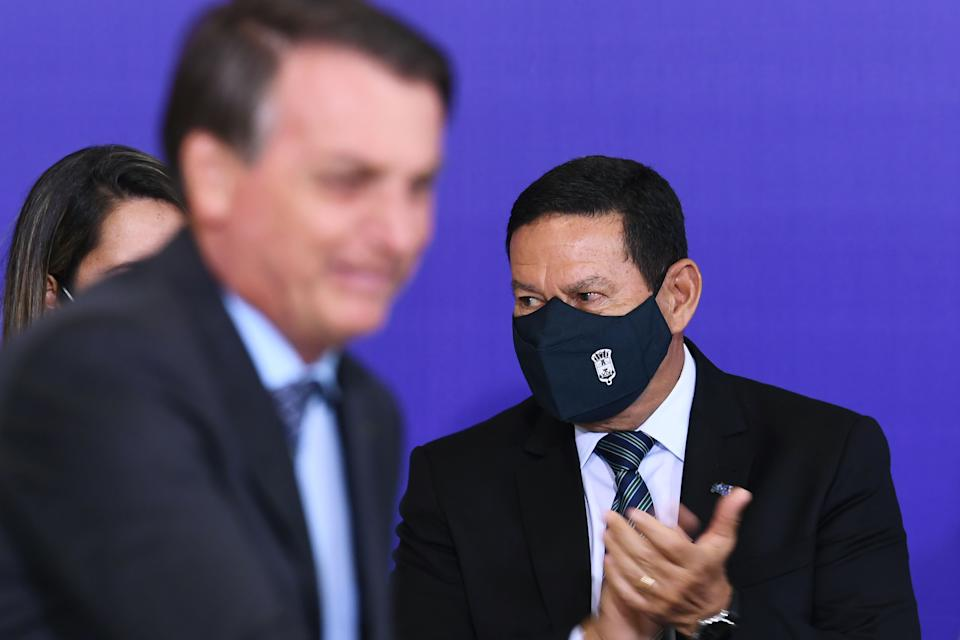 Brazilian Vice-President Hamilton Mourao applauds next to Brazilian President Jair Bolsonaro (R) during the launch of the Alliance for Volunteering aid program at Planalto Palace in Brasilia, on November 9, 2020, amid the new coronavirus pandemic. - Bolsonaro, even after 48 hours of confirmation of Joe Biden's victory in the US election, remains without making any comment on the issue. (Photo by EVARISTO SA / AFP) (Photo by EVARISTO SA/AFP via Getty Images)