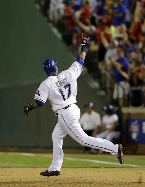 Texas Rangers' Nelson Cruz celebrates as he rounds first on his two-run home run off of Oakland Athletics relief pitcher Jesse Chavez in the fifth inning of a baseball game Monday, June 17, 2013, in Arlington, Texas. The home run also scored A.J. Pierzynski. (AP Photo/Tony Gutierrez)