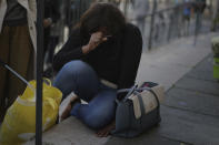 A woman reacts in front of Notre Dame church in Nice, France, Friday, Oct. 30, 2020. A new suspect is in custody in the investigation into a gruesome attack by a Tunisian man who killed three people in a French church. France heightened its security alert amid religious and geopolitical tensions around cartoons mocking the Muslim prophet. (AP Photo/Daniel Cole)