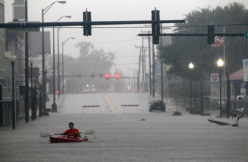 A man paddles through flood waters from Tropical Storm Debby in downtown Live Oak, Fla. on Tuesday, June 26, 2012. The National Hurricane Center says Debby has weakened to a tropical depression as it continues to move across Florida, bringing flooding to many areas. (AP Photo/The Gainesville Sun, Matt Stamey)