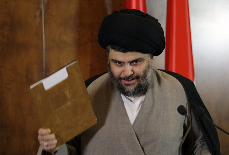 Shiite cleric Muqtada al-Sadr holds what he called a solution paper for Iraq's political crisis during a press conference in Irbil, a city in the Kurdish controlled north 217 miles (350 kilometers) north of Baghdad, Iraq, Thursday, April 26, 2012. A hardline Shiite cleric is meeting with the president of Iraq's Kurdish region to try to end a political crisis that has deadlocked the nation's government. Anti-American cleric Muqtada al-Sadr offered plans Thursday to resolve the impasse through political inclusiveness.(AP Photo/Khalid Mohammed)