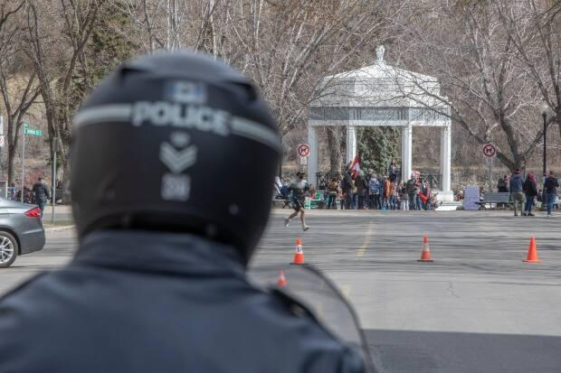 A Saskatoon police officer watches attendees from a distance at a rally against pandemic restrictions held at the Vimy Memorial at Kiwanis Park in Saskatoon on April 24. (Kayle Neis/The Canadian Press - image credit)