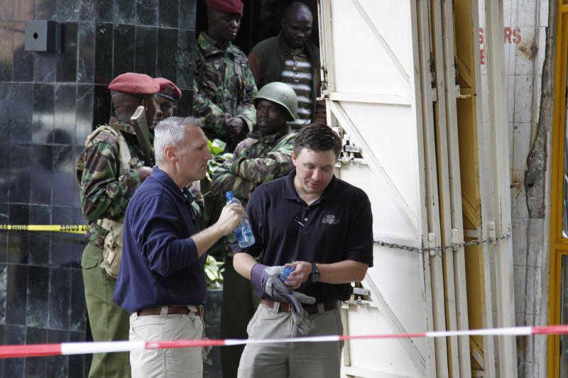 """Kenya paramilitary soldiers secure the area as American Investigators, work at the site of the explosion to assist Kenyan officials, in Nairobi, Kenya, Monday, May 29, 2012, in the investigation into a large explosion in Nairobi Monday. An explosion ripped through a building full of small shops in Nairobi, injuring at least 33 people, including a woman who blamed the blast on a """"bearded man"""" who left behind a bag shortly before the detonation. (AP Photo/Khalil Senosi)"""