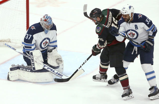 Winnipeg Jets goaltender Connor Hellebuyck (37) makes a save on a shot by Arizona Coyotes center Brad Richardson (15) as Winnipeg Jets defenseman Dustin Byfuglien (33) gives Richardson a push during the second period of an NHL hockey game Saturday, April 6, 2019, in Glendale, Ariz. (AP Photo/Ross D. Franklin)
