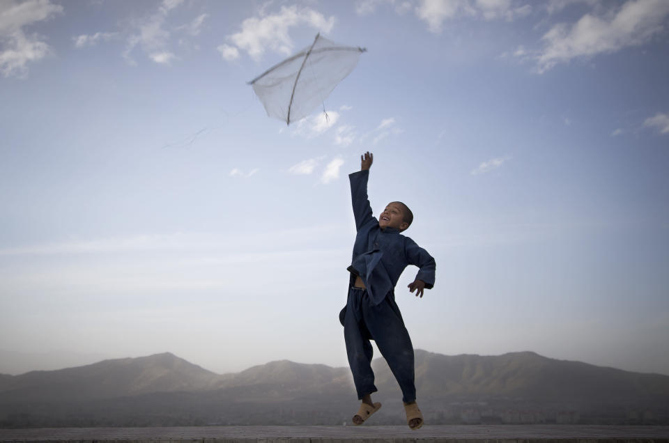 FILE - In this May 13, 2013 file photo, a boy flies his kite on a hill overlooking Kabul, Afghanistan. Kite flying was banned during the Taliban regime. (AP Photo/Anja Niedringhaus, File)