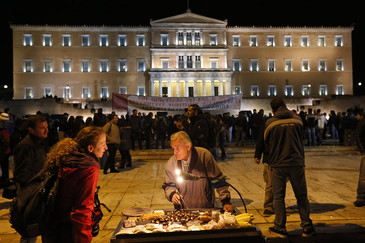 Thousands of protesters converged peacefully on the Greek capital's main square outside the Parliament as lawmakers debated the 2013 budget, which includes pension and salary cuts demanded by the country's international creditors in order for them to approve the next vital batch of rescue loans.