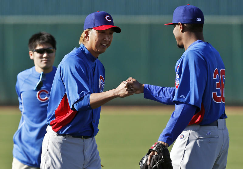 FILE - In this Feb. 12, 2013 file photo, Chicago Cubs' Kyuji Fujikawa, center, of Japan, gets a fist bump from teammate Edwin Jackson, right, as interpreter Ryo Shinkawa looks on during a spring training baseball workout  in Mesa, Ariz. A new rule in Major League Baseball that lets interpreters join managers and coaches on the mound when pitchers aren't fluent in English might still need some tweaking. The rule has already been used in spring training. (AP Photo/Ross D. Franklin, File)