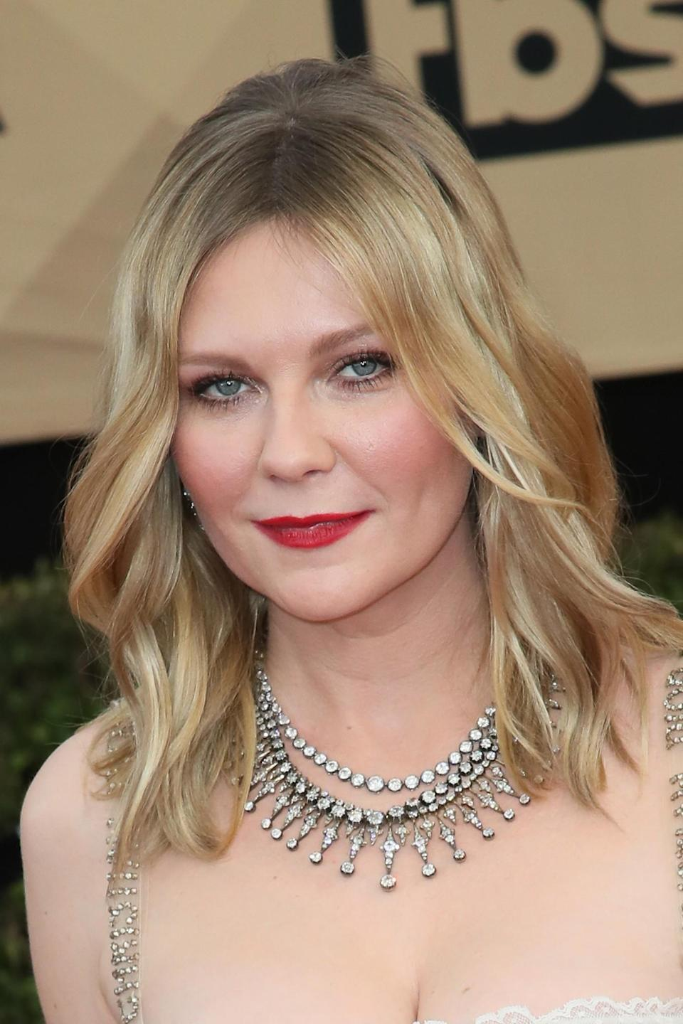 <p>Kirsten Dunst went for a classic look complimenting her bleach blonde locks with a bold red lipstick. [Photo: Getty] </p>