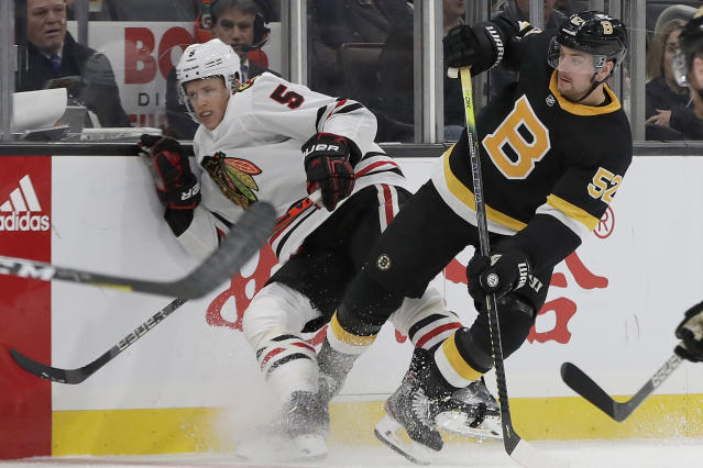 Chicago Blackhawks defenseman Connor Murphy (5) and Boston Bruins center Sean Kuraly (52) fight for position along the boards in the second period of an NHL hockey game, Thursday, Dec. 5, 2019, in Boston. (AP Photo/Elise Amendola)