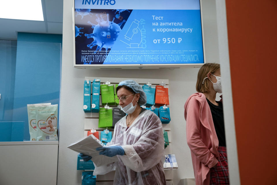An employee, left, works at one of Invitro's drop-in clinics for antibody testing in Moscow, Russia, Friday, Aug. 13, 2021. In Russia, it's common to get an antibody test for the coronavirus and share the results. The tests are cheap, widely available and actively marketed by private clinics nationwide, and their use appears to be a factor in the country's low vaccination rate even as daily deaths and infections are rising again. (AP Photo/Alexander Zemlianichenko)