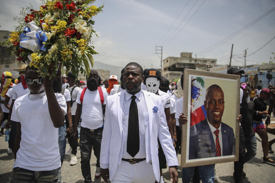 """Jimmy Cherizier, alias Barbecue, a former police officer who heads a gang coalition known as """"G9 Family and Allies,"""" march during a rally to demand justice for slain Haitian President Jovenel Moise in Lower Delmas, a district of Port-au-Prince, Haiti Monday, July 26, 2021. Moise was assassinated on July 7 at his home. (AP Photo / Joseph Odelyn)"""