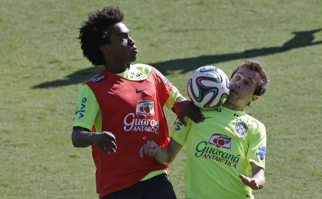 Brazil's Bernard, right, and Willian, train one day before his team's round of 16 World Cup soccer match with Chile at Mineirao Stadium in Belo Horizonte, Brazil, Friday, June 27, 2014. (AP Photo/Andre Penner)