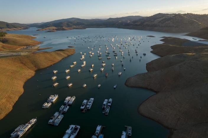 """<div class=""""inline-image__caption""""><p>Steep banks surround boats on Oroville Lake during low water levels in Oroville, California, U.S., on Tuesday, June 22, 2021. </p></div> <div class=""""inline-image__credit"""">Kyle Grillot/Bloomberg via Getty</div>"""