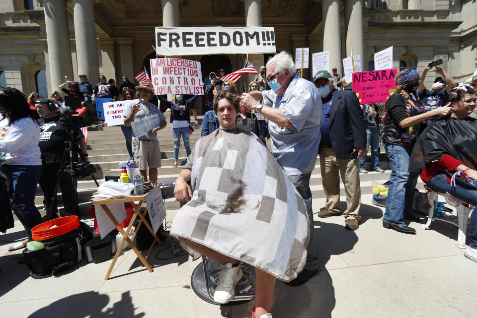 Barber Karl Manke, of Owosso, gives a free haircut to Parker Shonts on the steps of the State Capitol during a rally in Lansing, Mich., Wednesday, May 20, 2020. from the new coronavirus COVID-19. Barbers and hair stylists are protesting the state's stay-at-home orders, a defiant demonstration that reflects how salons have become a symbol for small businesses that are eager to reopen two months after the COVID-19 pandemic began. (AP Photo/Paul Sancya)