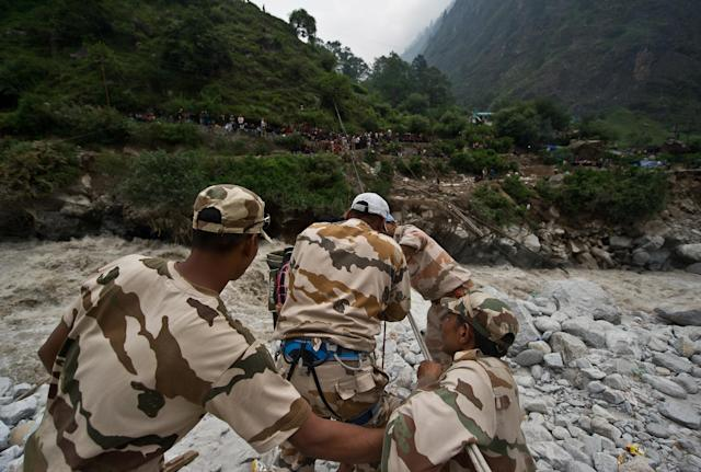 Indo-Tibetan Border Police (ITBP) personnel use a rope rescue system to transport stranded pilgrims across a river in Govind Ghat on June 23, 2013. Bad weather hampered rescue operations June 23 in northern India where up to 1,000 people are feared to have died in landslides and flash floods that have left pilgrims and tourists stranded without food or water. AFP PHOTO/MANAN VATSYAYANA