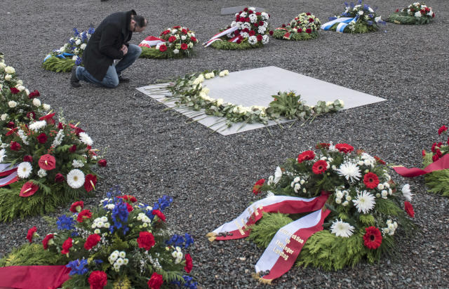 <p>A man kneels besides a plain metal plaque after a wreath-laying ceremony on occasion of the international Holocaust remembrance day in the former Nazi concentration camp Buchenwald near Weimar, Germany, Friday, Jan. 26, 2018. (Photo: Jens Meyer/AP) </p>