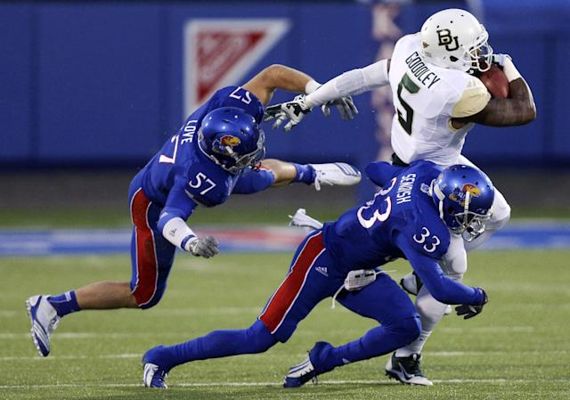 Baylor Bears wide receiver Antwan Goodley catches a pass against Kansas Jayhawks linebacker Jake Love (57) and Cassius Sendish (33) in the first quarter of an NCAA college football game Saturday, Oct. 26, 2013, in Lawrence, Kan. (AP Photo/Ed Zurga)