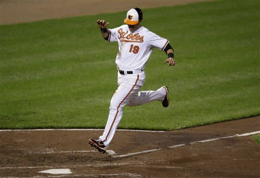 Baltimore Orioles' Chris Davis scores a run on a sacrifice fly by Ryan Flaherty in the fifth inning of a baseball game against the Toronto Blue Jays in Baltimore, Thursday, April 26, 2012. Baltimore won 5-2. (AP Photo/Patrick Semansky)