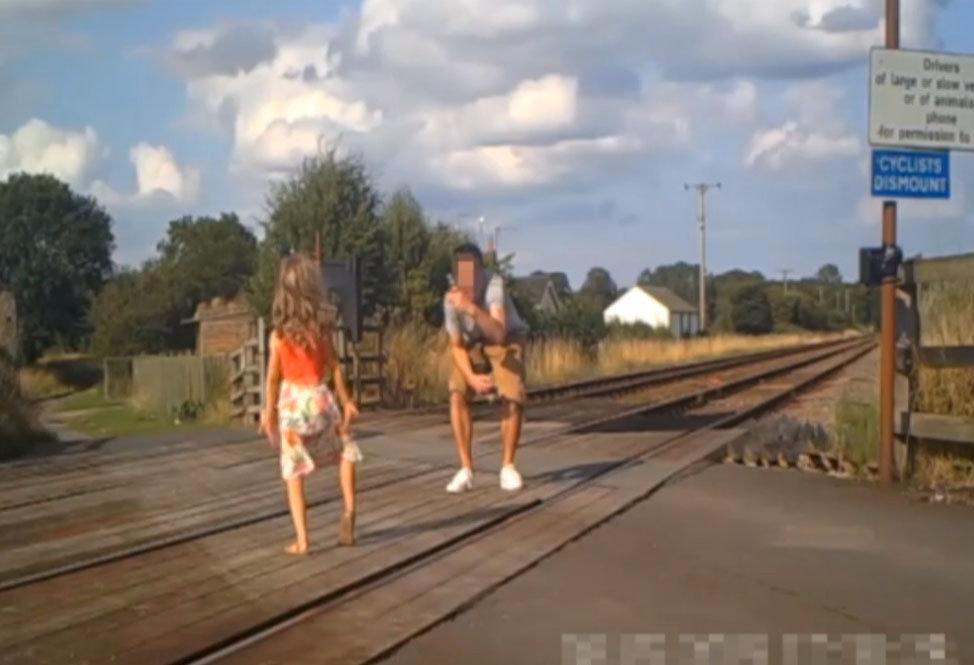 Shocking CCTV footage has been released which shows people risking their lives on level crossings - including a father and his young daughter posing for a photo shoot. The reckless father can be seen taking pictures of the little girl - who appears to be of primary school age - in different directions on the crossing. Their car can be seen in the background with its doors open as the youngster adopts various poses and occasionally looks behind her for approaching trains. Another shocking clip captured on CCTV shows a group of cyclists who dismount their bikes and line up for a group photo on the crossing.
