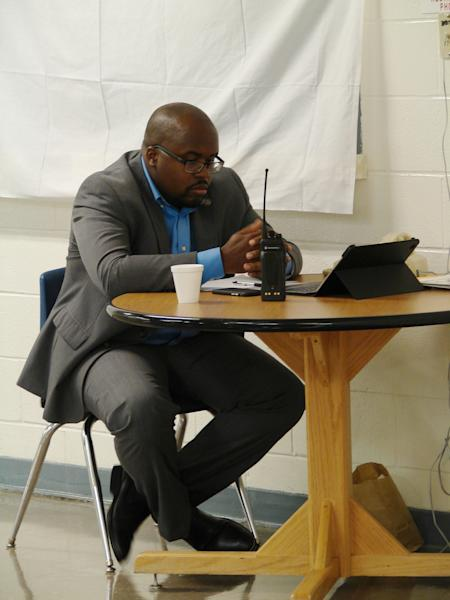 Solomon Graves, a spokesman for the Arkansas Department of Correction, waits at a desk for a telephone call with news from the death chamber at the Cummins Unit prison near Varner, Ark., on Thursday, April 20, 2017. The U.S. Supreme Court rejected stay requests from Ledell Lee, allowing his execution to proceed at the prison. (AP Photo/Kelly P. Kissel)