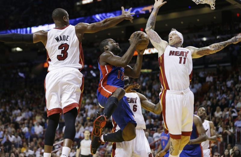 Detroit Pistons' Will Bynum (12) goes between Miami Heat players Dwyane Wade (3) and Chris Anderson (11) for a lay up during the second half of a NBA basketball game in Miami, Friday, March 22, 2013. The Heat won 103-89. (AP Photo/J Pat Carter)