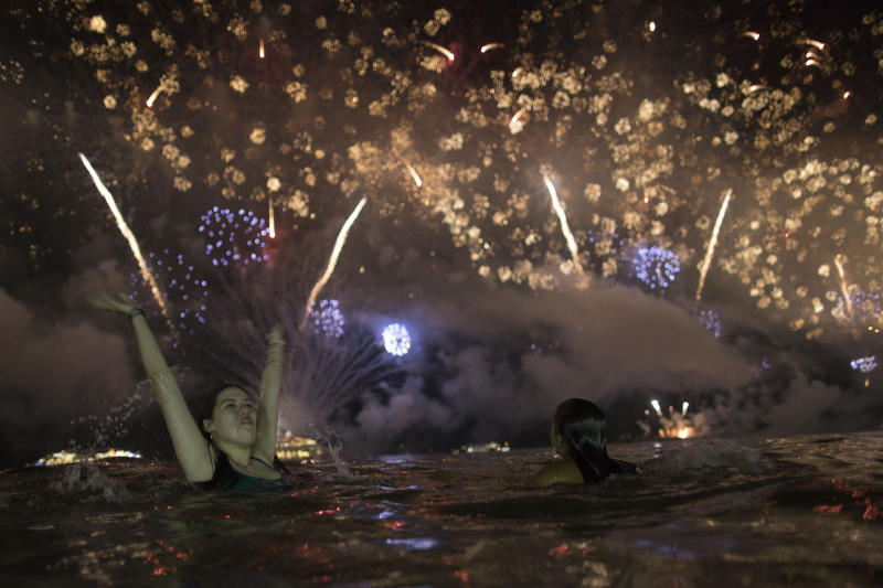 A woman watches the fireworks exploding over Copacabana Beach during the New Year's celebrations in Rio de Janeiro, Brazil