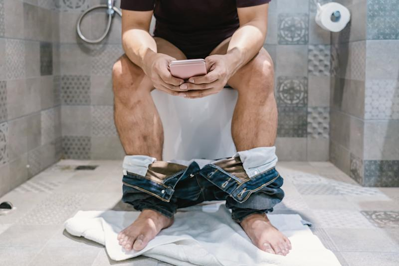 Low Section Of Man Using Mobile Phone While Sitting In Bathroom