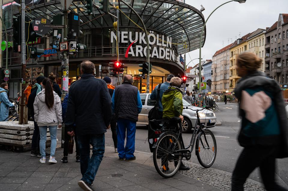 15 October 2020, Berlin: People wait at a red light in front of the Neukölln Arcaden shopping centre. In Neukölln, the number of coronavirus infections has been rising for several days. Photo: Christophe Gateau/dpa (Photo by Christophe Gateau/picture alliance via Getty Images)