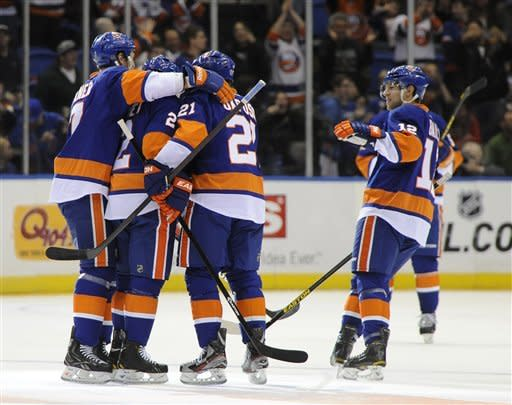New York Islanders' Josh Bailey (12) skates in to celebrate Mark Streit's (2) goal against the Pittsburgh Penguins with teammate's Matt Carkner (7) and Kyle Okposo (21) during the first period of an NHL hockey game on Friday, March 22, 2013 at Nassau Coliseum in Uniondale, N.Y. (AP Photo/Kathy Kmonicek)