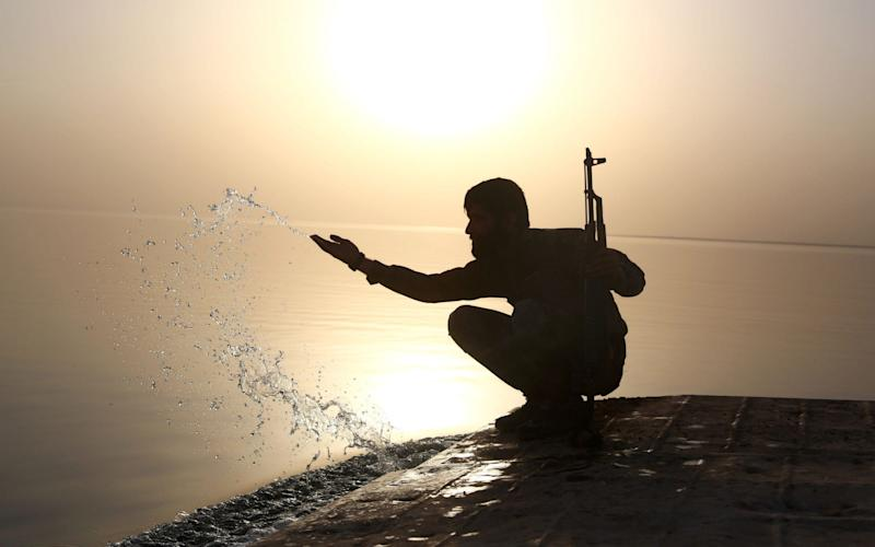 A member of the US-backed Syrian Democratic Forces (SDF) splashes water at the Tabqa dam on April 29 - AFP