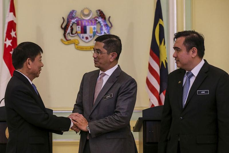 Minister of Economic Affairs Datuk Seri Mohamed Azmin Ali (centre) shakes hands with Singapore Transport Minister Khaw Boon Wan during a news conference in Putrajaya September 5, 2018. ― Picture by Hari Anggara