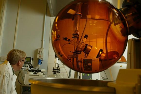 Laboratory with person in white coat looking at amber-colored sphere suspended in the air.