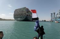 A man waves an Egyptian flag as ship Ever Given, one of the world's largest container ships, is seen after it was fully floated in Suez Canal