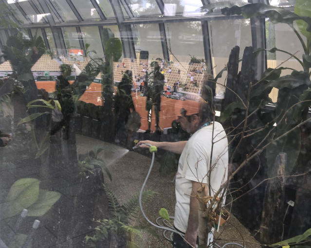 A gardener waters tropical plants in the greenhouses that surround the new Simonne Mathieu court prior to the first round matches of the French Open tennis tournament at the Roland Garros stadium in Paris, Sunday, May 26, 2019. (AP Photo/John Leicester)