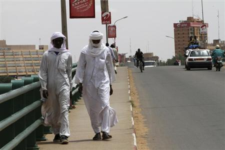 People walk along Kennedy Bridge in Niamey