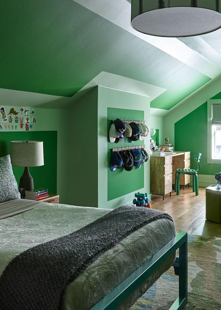 """This son's bedroom occupies a cozy attic space. """"He wanted green walls,"""" says Liss. """"The ceilings were so low that we decided to paint them green too, and created geometric shapes."""" The designer used Sherwin Williams's Envy and Relish shades."""