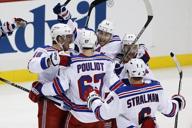 New York Rangers' Derick Brassard (16) celebrates his game-winning goal with teammates in the first overtime period of Game 1 of a second-round NHL hockey playoff series against the Pittsburgh Penguins in Pittsburgh, Friday, May 2, 2014. The Rangers won 3-2. (AP Photo/Gene J. Puskar)