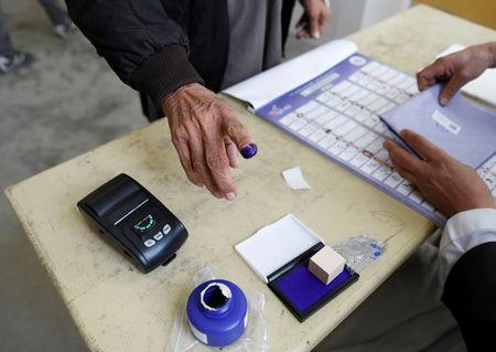 FILE PHOTO: An election official assists an Afghan man at a polling station during a parliamentary election in Kabul