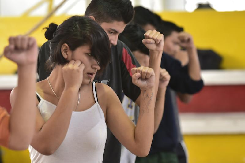 Any Hurtado (L) takes a part in boxing training in a gym in downtown Quito on August 18, 2014