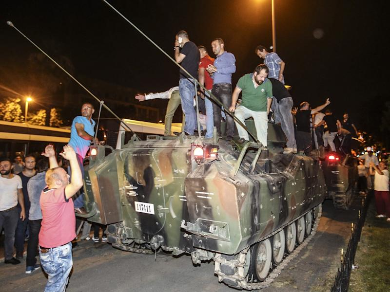 Turkish citizens, taking to the streets to react against a failed military coup attempt after Turkish President Recep Tayyip Erdogan called on people to defend democracy, on a tank as they intervene and block armoured vehicles of soldiers at Vatan street in Istanbul, Turkey in 2016.