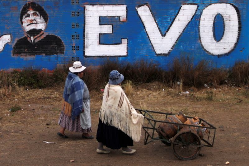 Women walk past a wall with a graffiti depicting former Bolivian President Evo Morales, before general elections in La Paz